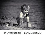 sandy beach. little boy plays... | Shutterstock . vector #1142035520