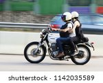 Small photo of A biker riding a Honda CB400 motorcycle with a passenger on the Hiram's Highway in Sai Kung Hong Kong and with blur movement, Photo taken on 25 July 2018