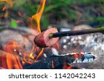 cooking sausage on a stick over ... | Shutterstock . vector #1142042243
