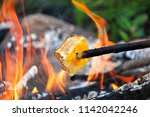grilling cheese over a fire | Shutterstock . vector #1142042246