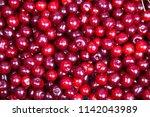 background of red ripe cherries.... | Shutterstock . vector #1142043989