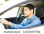 attractive young man driving a... | Shutterstock . vector #1142047556