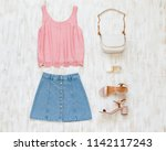 Pink tank top, blue denim mini skirt, small white cross body bag with chain strap, pink block heeled sandals on white wooden background. Woman
