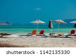view at parasol and sunbeds at... | Shutterstock . vector #1142135330