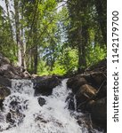 a small waterfall pours down... | Shutterstock . vector #1142179700
