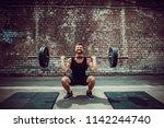 muscular fitness man doing... | Shutterstock . vector #1142244740