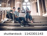 Students are spending time together.Multiethnic group of young people looking at a laptop and and sitting on steps in university hal