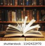 old open book on a bookshelf... | Shutterstock . vector #1142422970
