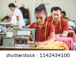 Small photo of portrait of professional Seamstress in textile factory sewing with industrial sewing machine at garment