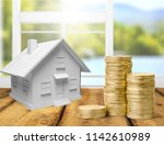 house model and coin money on... | Shutterstock . vector #1142610989