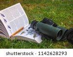 binoculars and bird guide | Shutterstock . vector #1142628293