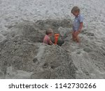 children dig a hole in the sand ... | Shutterstock . vector #1142730266