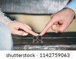 bride and groom holding rings... | Shutterstock . vector #1142759063