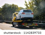 tow truck with a car on the road | Shutterstock . vector #1142839733