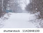 snowy rural street during... | Shutterstock . vector #1142848100