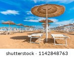 straw sun umbrellas on beach.... | Shutterstock . vector #1142848763
