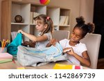 two little girls packing their... | Shutterstock . vector #1142869739