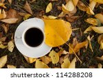 coffee cup and yellow autumn leaf - stock photo