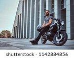 brutal bearded male in a gray t ... | Shutterstock . vector #1142884856
