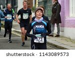 Small photo of Hastings,East Sussex/UK 03-18-18 Hastings half marathon 2018. Manda running for Prostate cancer UK sprints down All Saints Street in the old town pursued by other competitors