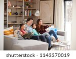 family relaxing on sofa at home ... | Shutterstock . vector #1143370019