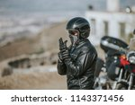 man in motorcycling clothes... | Shutterstock . vector #1143371456