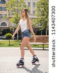 young stylish woman skating on... | Shutterstock . vector #1143407300