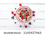 oatmeal with yogurt and berries.... | Shutterstock . vector #1143427463