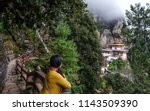 a woman looking at the taktsang ... | Shutterstock . vector #1143509390