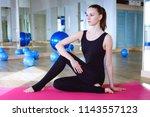 woman sitting on pink ypga matt ... | Shutterstock . vector #1143557123
