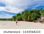 man walking along the coral... | Shutterstock . vector #1143568223