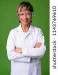 Mature beautiful multi-ethnic woman doctor wearing protective glasses