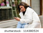 Portrait of beautiful young woman in urban background talking on phone - stock photo