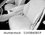 Stock photo white leather interior of the luxury modern car leather comfortable white seats and multimedia 1143860819