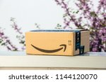 Small photo of PARIS, FRANCE - APR 19, 2018: Side view of new Amazon Cardboard box left outdoor the house by courier with large Amazon Smile logotype against defocused tree background