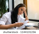 stressed young asian woman... | Shutterstock . vector #1144131236