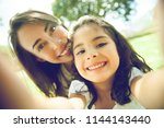 mom and daughter taking a... | Shutterstock . vector #1144143440