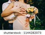 the bridegroom embraces the... | Shutterstock . vector #1144282073