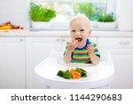 cute baby eating vegetables in... | Shutterstock . vector #1144290683