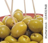 closeup of a plate with olives with toothpicks served as tapas on a white background - stock photo