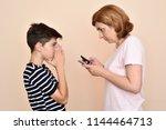mother checking two smartphones ... | Shutterstock . vector #1144464713