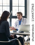 young devoted doctor holding an ... | Shutterstock . vector #1144472963