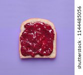 Small photo of Toast slice with fruit jam on a purple background viewed from above. Slice of bread with raspberry marmalade isolated on a colorful background. Top view