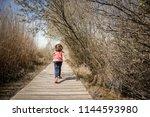 little girl walking on a path... | Shutterstock . vector #1144593980