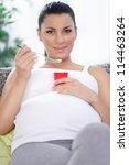 Smiling pregnant woman eating fruit yogurt, tasty and useful - stock photo