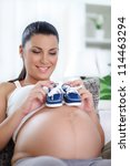 smiling pregnant woman with two little baby shoes on her belly - stock photo