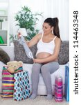Young pregnant woman at home with shopping bags - stock photo