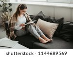 Concentrated woman sits on sofa ...