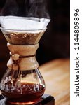 Small photo of chemex with hot coffee. close up portrait.chemex containing brewed joe