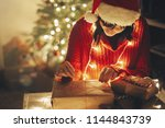 merry christmas. girl wrapping... | Shutterstock . vector #1144843739